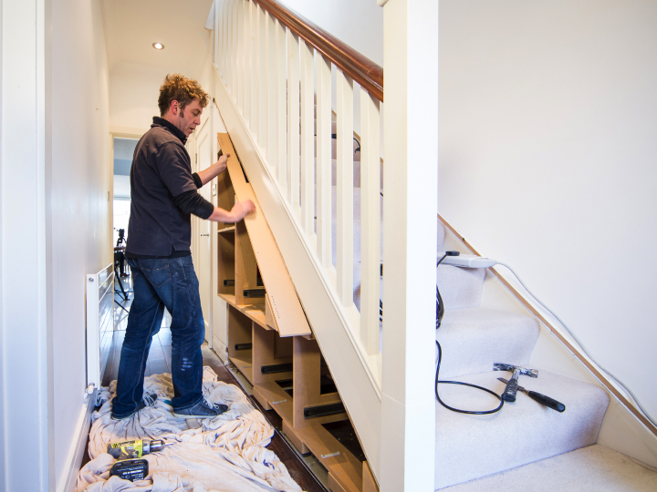 Tradesman Installing an Under Stair Flat Pack Unit